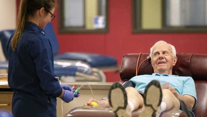 Emily Anderson collects a blood donation from Robert Hietpas on Wednesday at the Community Blood Center in Grand Chute.