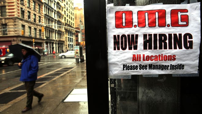 A sign in a window at a retail store advertises for a job opening.