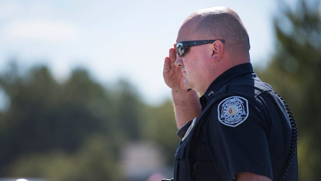 A Mauldin police officer salutes at an October 2017 burial service at First Baptist Church Mauldin.
