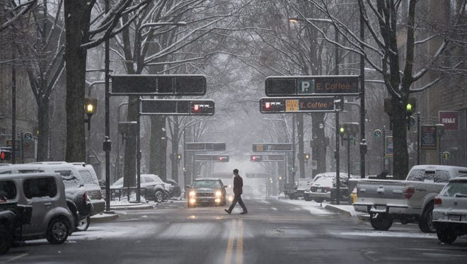 A person crosses Main Street in downtown Greenville as snow falls on Wednesday, January 17, 2018.