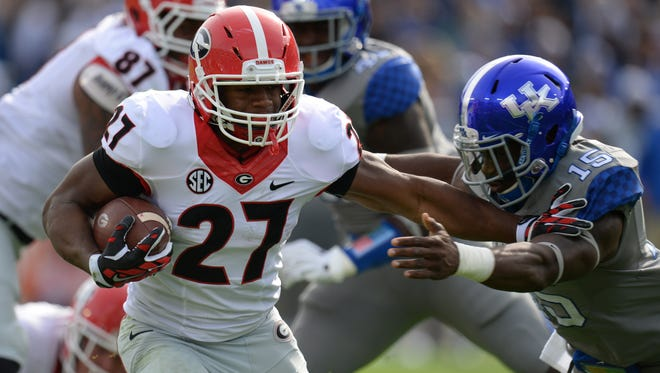 Georgia running back, Nick Chubb, straight arms UK safety, Marcus McWilson, during the University of Kentucky football game against the University of Georgia at Commonwealth Stadium in Lexington, Ky. Saturday, November 8, 2014.