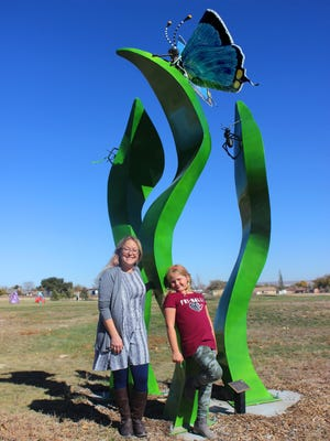 Volunteer Michelle Whitaker (left) and her daughter Lily, 10, pose by one of the statues the Pueblo West Women's League donated to Civic Center Park.