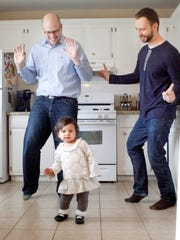 Leah Rose, 16 months, dances in the kitchen with her fathers Brett Parlock, left, and Kevin Schaefer at their Frankfort, Ill., home.