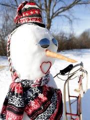 Dennis and Linda Hemauer make snowmen in their yard