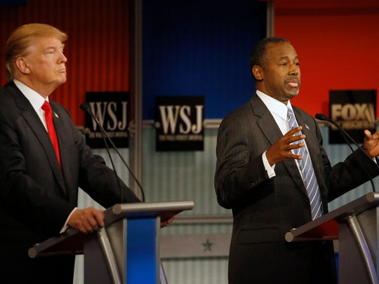 Ben Carson, right, speaks as Donald Trump listens during Republican presidential debate at Milwaukee Theatre, Tuesday, in Milwaukee.