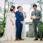 Blake Keng, right, reads from Supreme Court Justice Anthony Kennedy's opinion on same-sex marriage during the wedding Saturday of Jillian Levine Smith, left, and Emily Smith.