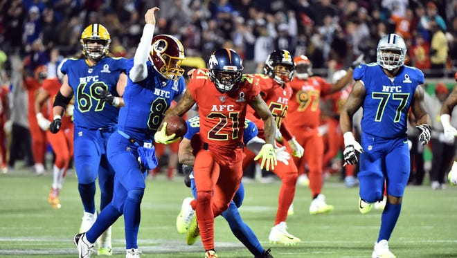 NFC quarterback Kirk Cousins of the Washington Redskins (8) knocks the ball loose from AFC cornerback Aqib Talib of the Denver Broncos (21) during the second half at the 2017 Pro Bowl at Citrus Bowl.