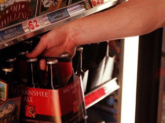 A customer pulls a six pack of H.C. Berger's Red Banshee Ale off a shelf in 2000.