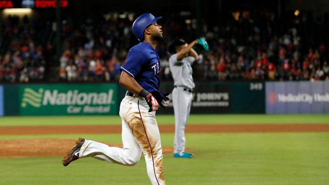 Texas Rangers' Elvis Andrus jogs home past Seattle Mariners' Ariel Miranda after hitting a two-run home run in the sixth inning of Wednesday's game.