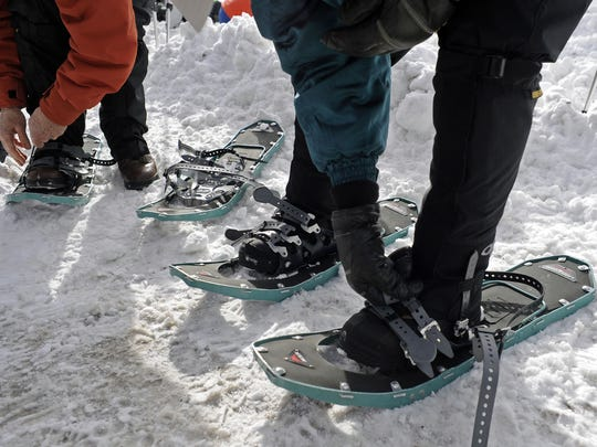Beginning snowshoers put on their snowshoes prior to heading into the wilderness near Boreal in 2009.