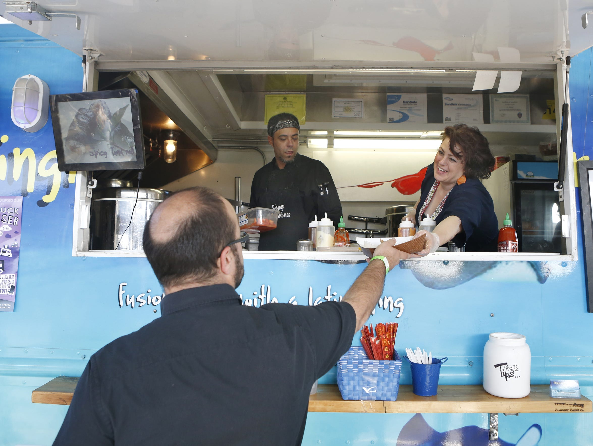"""File photo: Kimberly Roth of The Stingray Sushifusion truck serves a customer as co-owner Radhames """"Rod"""" Veras looks on."""