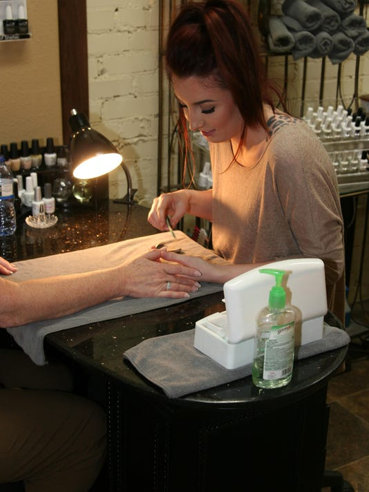 Paige Leiders performs a manicure on a customer.