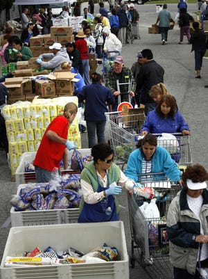 Lupe Caballero center foreground in green, a volunteer for the Food Bank for Monterey County, hands out food to people going through the food line in this file photo.