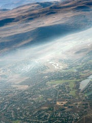 "In this aerial photo, smoke hovers above the city of Reno, Nev. Wednesday, Sept. 24, 2014. Crews in California have been fighting the King Fire, east of Sacramento, which is threatening thousands of homes and prompting ""dense smoke advisories"" across the region.  (AP Photo/Martha Irvine)"