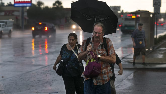 Jay Jones of Phoenix tries to stay dry under heavy rains as winds force back his umbrella while walking along Thomas Road near 36th Street in Phoenix during the monsoon storm on July 9, 2018.