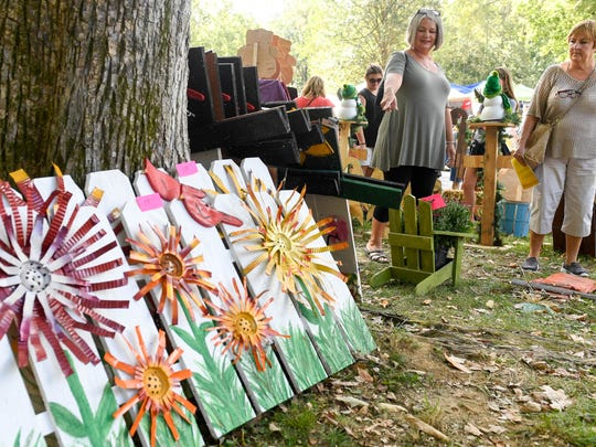 Gena DeLamar (left) and Terry Alloway shop for yard art at the 45th annual Lions Arts and Crafts Festival in Henderson's Audubon State Park Saturday. The event continues all day Sunday, October 7, 2017.