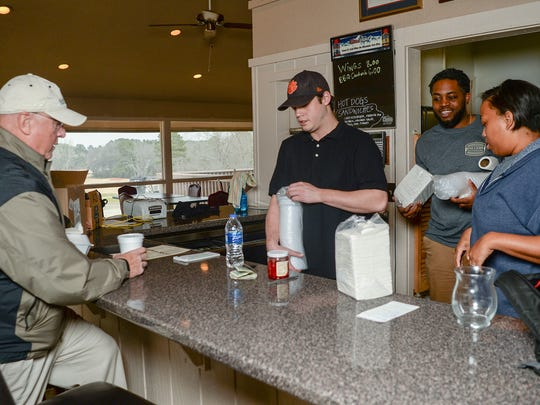 Greg Henning of Salem, left, orders a lunch with Andres Johnson, middle, near Stormy Mattison, middle right, and Kiara Johnson, right, at Grits and Gravy restaurant, in the clubhouse of Cobbs Glen Country Club in Anderson on Thursday.