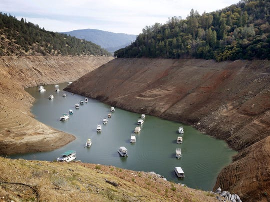 Houseboats float in the drought-lowered waters of Oroville Lake near Oroville in 2014. Lake Oroville, the State Water Project's principal reservoir, was dipping toward its record low set in 1977. President Donald Trump has ordered the government to streamline regulations that he says are hindering work on four major water projects in the Western United States. Trump signed a memorandum Friday, Oct. 19,2018 aimed at helping the Central Valley Project and the California State Water Project in California, the Klamath Irrigation Project in Oregon and the federal Columbia River system in the Pacific Northwest. (AP Photo/Rich Pedroncelli, File)