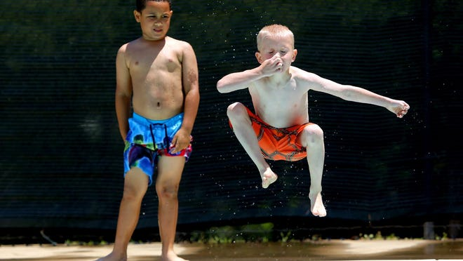 Jamier Johnson watches as Xavier Iacount jumps in the Shelby City Park pool.