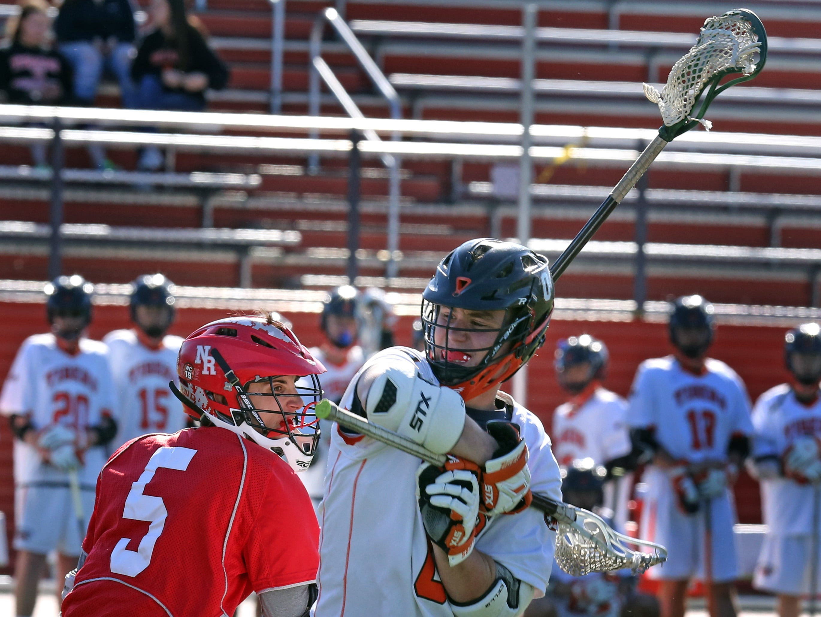North Rockland's James Morina (5) guards White Plains Brendan Johnson (0) during boys lacrosse Section 1 Class A opening-round game at White Plains High School on May 16, 2016. White Plains defeats North Rockland 13-12.