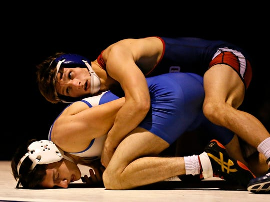 New Oxford's Zurich Storm, top, captured his first District 3 3-A title, winning the 120-pound weight class on Saturday over Central Dauphin's Chris Wright. Dawn J. Sagert photo