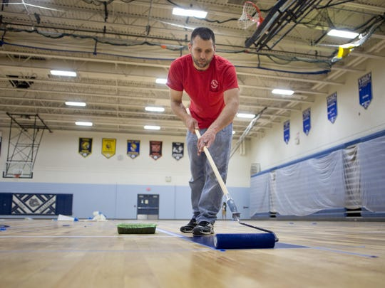 Chris VanDerStelt works on refinishing and painting the gym floor Tuesday, July 21, 2015 at Yale High School. Voters will be asked to renew the 1 mill sinking fund on August 4, which will generate approximately $1.8 million over five years.
