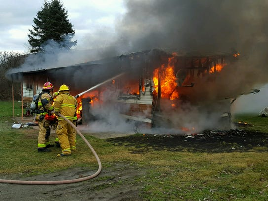 Fire crews work to extinguish a fully engulfed mobile