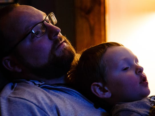 Ford Lillard spends time on the couch with his son Hunter, 5, after work and school on Tuesday, Dec. 12, 2017, in Wiota. Ford grew up in the small town and is now the volunteer fire chief and mayor. He is trying to make the town more attractive to younger families and has spearheaded an effort to bring a better water system to town as a way to get started.