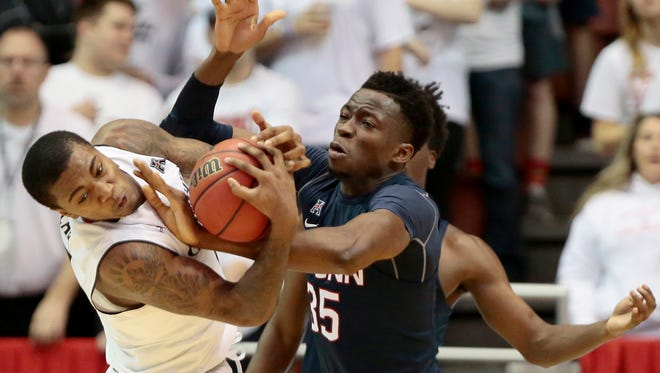 Cincinnati Bearcats forward Gary Clark (11) and Connecticut Huskies center Amida Brimah (35) struggle for a jump ball in the second half of the NCAA basketball game between the Cincinnati Bearcats and the Connecticut Huskies at Fifth Third Arena on the campus of the University of Cincinnati in Cincinnati on Saturday, Feb. 20, 2016. The Bearcats defeated the Huskies 65-60 for their 20th win of the season.