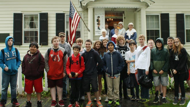 Seventh-graders stand in front of the Daughters of the American Revolution Chapter House in Rhinebeck.