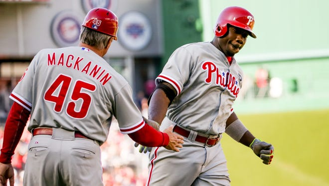 Phillies first baseman Ryan Howard is congratulated by Phillies third base coach Pete Mackanin after hitting a home run at the start of the fifth inning to put the Phillies up 7-0 against the Washington Nationals at Nationals Park on Saturday in Washington.