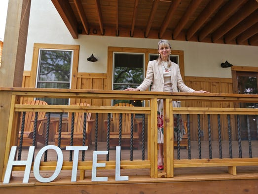 Hotel Broad Ripple owner Debbie Hasbrook stands on the porch of the hotel, Wednesday, May 21, 2014. The newly-opened nine-room boutique hotel is located on the Monon Trail in Broad Ripple.  Outdoor seating areas and porches are among the best features of the hotel.