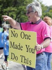 Dean Ekberg jokes with Bellin Run participants after they commented on his sign June 9, 2018 in Allouez, Wis.