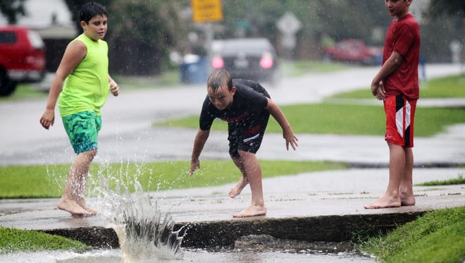 Jaren Trickey, 9, skims a boogie board across high water in a ditch along Mosser Drive in Lafayette as he competes with his brother Jace, 9, right, and their friend Mike Roberts, 9, to see who can get it to slide the farthest in the ditch during heavy rain showers Friday, July 18, 2014.