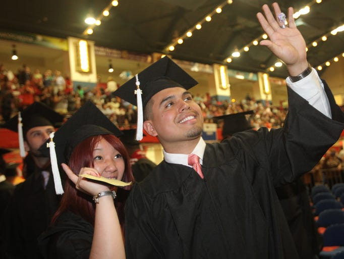 Gabrielle Do and Adrian Lopez wave to their family during Nyack College Graduation at Westchester County Center in White Plains May 10, 2014.