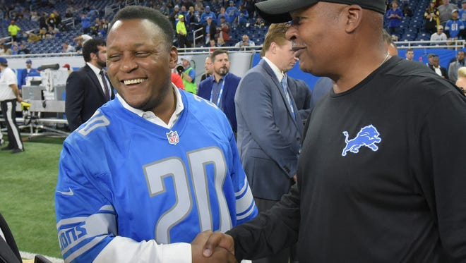 Detroit Hall of Fame running back Barry Sanders says hello to Lions coach Jim Caldwell on the sidelines with other former players before the game.