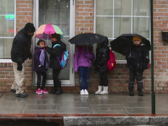 Children huddle under umbrellas as they wait for the