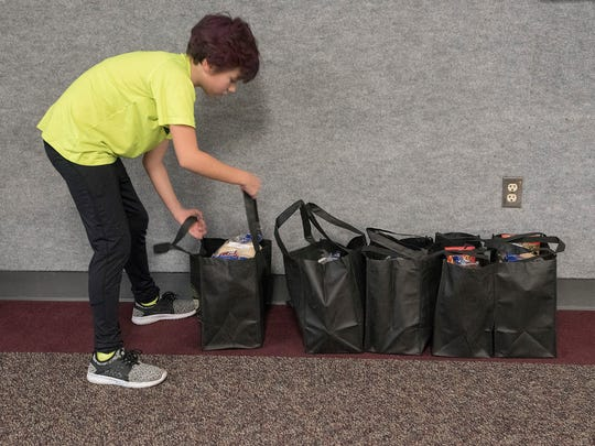 Linda O'Mara-Liske adds another full bag to the growing collection of Thanksgiving meals.