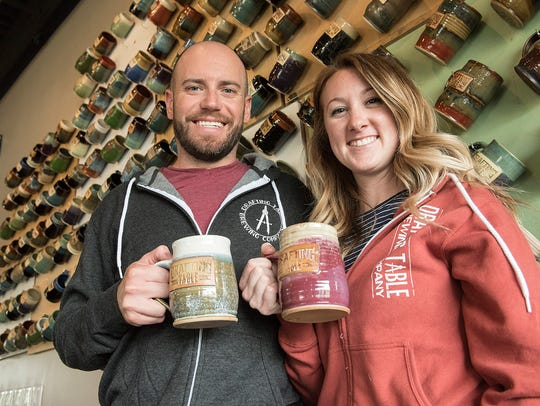 Aaron and Kristin Rzeznik, proprietors of Drafting Table Brewing Company show their personal beer steins. Patrons can join the brewery's mug club and have their own steins, too.