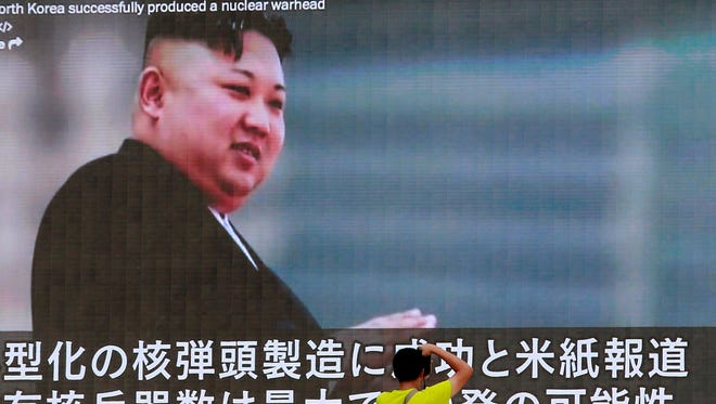 """A man takes a photo of a TV news program in Tokyo, showing an image of North Korean leader Kim Jong Un Wednesday, Aug. 9, 2017. In an exchange of threats, U.S. President Donald Trump warned Pyongyang of """"fire and fury like the world has never seen"""" and the North's military claimed Wednesday it was examining plans for attacking Guam."""