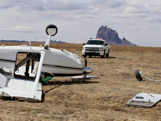 A small passenger plane sits off the runway after being