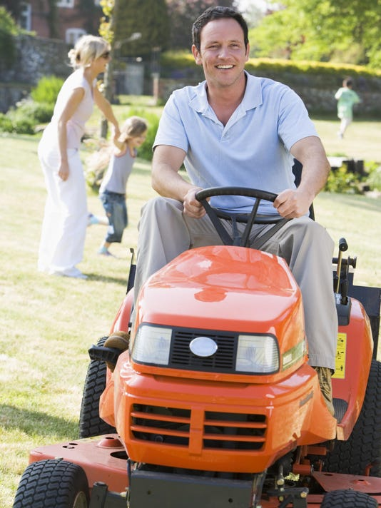Man outdoors driving lawnmower smiling with family in background