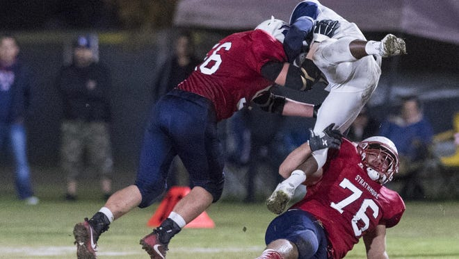 Strathmore nose tackle Lucas Raya (76) and Jadon Guire combine to bring down a Horizon Christian Academy ballcarrier during a CIF South Division G-A Regional Football Championship Bowl Game on Saturday, December 10, 2016.