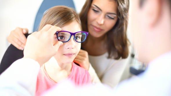 Little girl with her mother having her eyesight examined