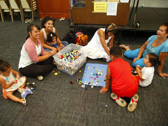 The Rodriguez family from Christ United Methodist Church, work together creating buildings out of Lego building blocks.