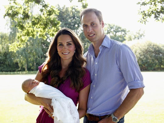 Duchess Kate of Cambridge and Prince William, Duke of Cambridge, pose with newborn Prince George in the garden of the Middleton family home in August 2013 in Bucklebury, Berkshire.