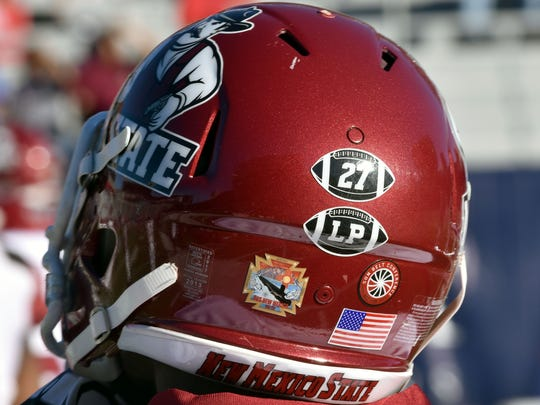 New Mexico State football players wore helmet decals on Friday to honor Aggies great Pervis Atkins, who passed away recently, and honorary team captain Lori Paulson, who passed away in 2016.