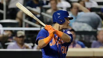 Mets' Michael Conforto follows through on a two-run single during the sixth inning of a baseball game against the Miami Marlins Saturday, Aug. 19, 2017, in New York.