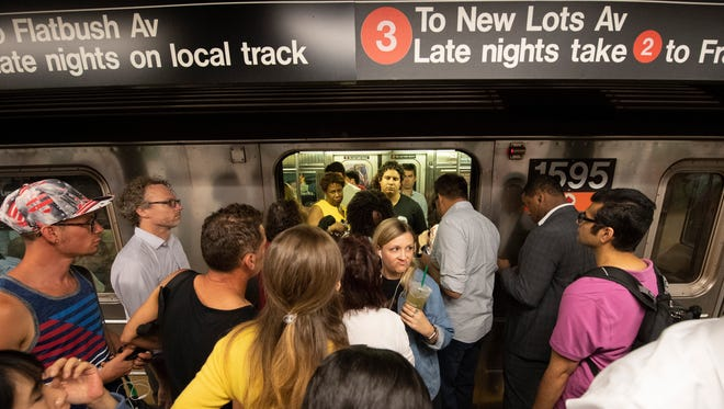 Passengers board a crowded subway train in Times Square.