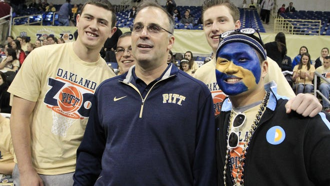 Pittsburgh football coach Pat Narduzzi poses for a photo with members of the Panthers' student section before a basketball game.